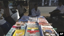 Newspapers and magazines are sold by vendor in a street in Rangoon, Burma, 06 Nov 2010