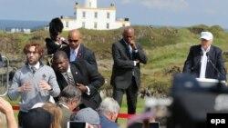Un homme manifeste avec une balle de golf rouge marquée d'une croix gammée pendant que le candidat républicain à la présidence américaine Donald Trump, à l'arrière droite, coiffé d'une casquette blanche, est sur le point de donner un discours sur la cours de golf Trump Turnberry, en Écosse, en Grande-Bretagne, 24 juin 2016.