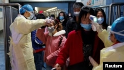 Medical workers take the temperature of passengers after they got off the train in Jiujiang, Jiangxi province, China, as the country is hit by an outbreak of a new coronavirus, January 29, 2020.