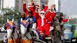 Para pria berpakaian Sinterklas untuk menyambut Natal di Lahore, Pakistan, Jumat (23/12). Pemerintah Pakistan juga meluncurkan kereta api khusus yang bertemakan Natal mulai Kamis (22/12) malam.