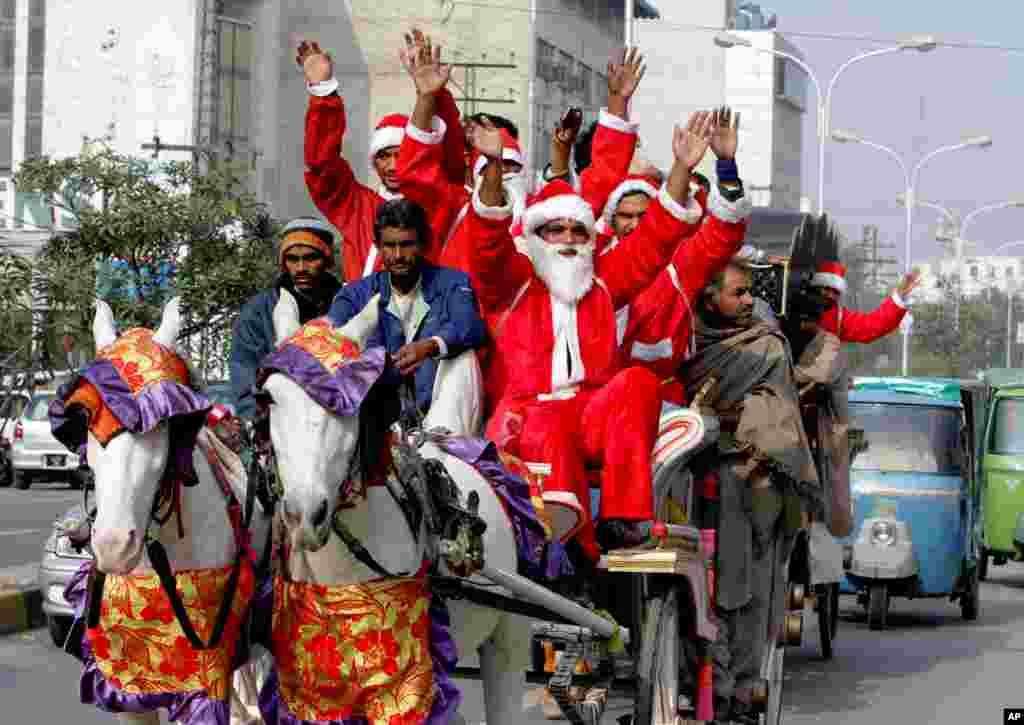 No Paquistão, homens vestido de Pai Natal passeiam pela rua numa carruagem. Lahore, Paquistão, Dez. 23, 2013.