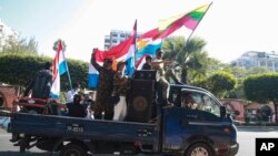 Supporters onboard a car wave national and military flags Tuesday, Feb. 2, 2021, in Yangon, Myanmar. Hundreds of members of Myanmar's Parliament remained confined inside their government housing in the country's capital on Tuesday, a day after the militar