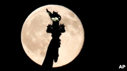 "In this July 31, 2015, file photo, a full moon rises behind the torch of the Statue of Liberty as seen from Liberty State Park in Jersey City, N.J. But what does it mean ""to carry a torch for someone""? Read on to find out! (AP Photo/Julio Cortez)"