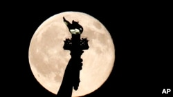 In this July 31, 2015, file photo, a blue moon rises behind the torch of the Statue of Liberty seen from Liberty State Park in Jersey City, N.J. A blue moon happens when the moon rises in its full stage twice during the same month. (AP Photo/Julio Cortez)