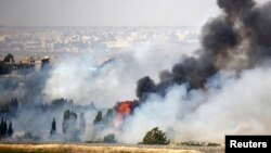Smoke rises as a fire burns near the Quneitra transit point, as seen from the Israeli occupied Golan Heights, close to the ceasefire line between Israel and Syria, June 6, 2013.