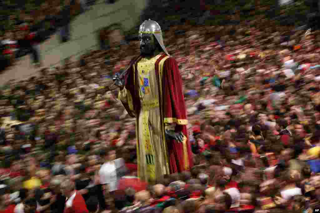 A figure of a giant stands as revellers take part in the Patum in the Catalan village of Berga, Spain. The Patum of Berga is a popular festival whose origin can be traced to medieval festivities that is celebrated each year in the Catalan city of Berga during Corpus Christi.