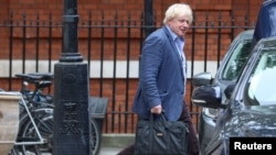 FILE - Former British foreign secretary Boris Johnson leaves his home at Carlton House Terrace, in central London, Britain, July 11, 2018.