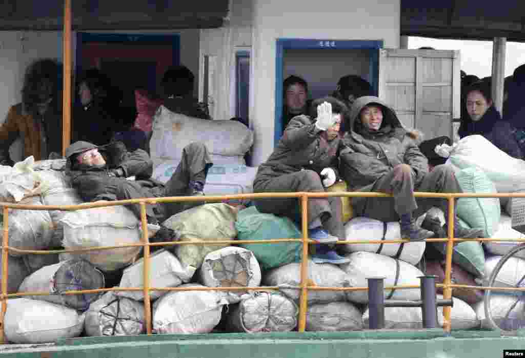 A North Korean man blocks his face with his hand from being photographed as he and other residents take a ferry in Yalu River, near the North Korean town of Sinuiju, opposite the Chinese border city of Dandong, April 11, 2013.