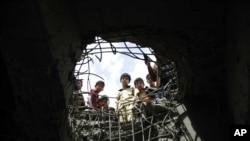 Anak-anak mengintip ke lubang akibat serangan udara yang dipimpin Saudi di jembatan di Sana'a, Yaman, 23 Maret 2016.