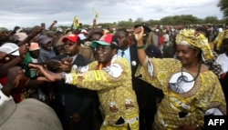 FILE: Zimbabwe's President Robert Mugabe (C) greets supporters with his wife Grace in Tsholotsho whilst on the campaign trail, 23 March 2005.