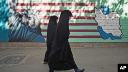 兩名伊朗婦女十月十二日在德黑蘭路過前美大使館的反美壁報
