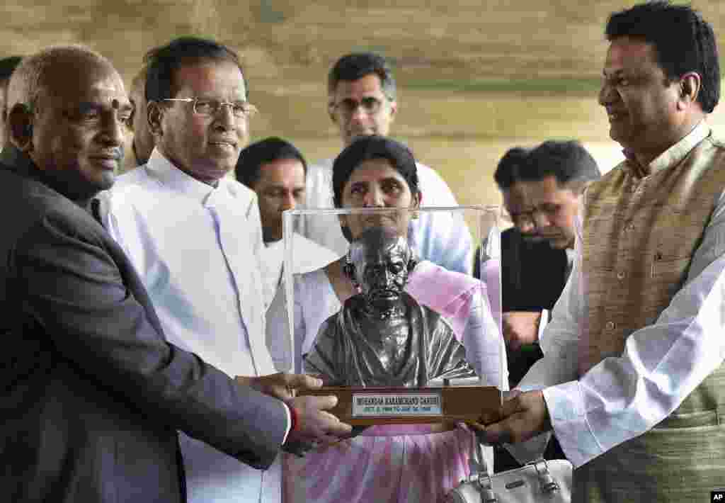 Sri Lankan President Maithripala Sirisena (second from left) and his wife Jayanthi Sirisena, receive a bust of Mahatma Gandhi during their visit to Rajghat, the memorial to the late Mahatma Gandhi, in New Delhi, Feb. 16, 2015.