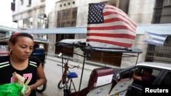 Havana'da Amerikan bayrağı tanan bir bisiklet taksi