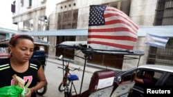 FILE - A woman walks past a bicycle taxi displaying the U.S. and Cuban flags in Havana, Dec. 17, 2014.