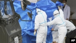 3月25日日本自卫队员运送被幅射水灼伤的两名工人