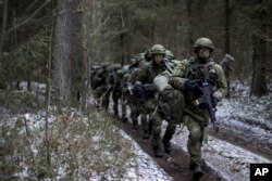 FILE - Lithuanian troops practice during a NATO military exercise, 'Iron Sword,' at the Rukla military base some 130 km. (80 miles) west of the capital Vilnius, Lithuania, on Nov. 28, 2016.