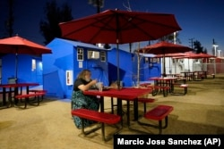A person living in the village eats at a community table, February 25, 2021, in the North Hollywood section of Los Angeles. (AP Photo/Marcio Jose Sanchez)