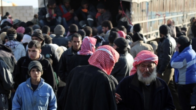 In this photo provided by Turkey's Islamic aid group of IHH, Syrians fleeing the conflicts in Azaz region, arrive in a truck at the Bab al-Salam border gate, Syria, Feb. 5, 2016.