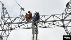 Deux agents de la société Eneo Cameroon effectuent des travaux, à Douala. (Crédit/Eneo)