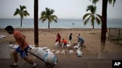 23일 멕시코 푸에르토발라르타 주민들이 허리케인 퍼트리샤에 대비해 해안 상가 주변에 모래주머니를 쌓고 있다.