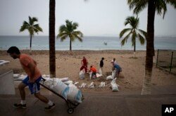 Residents prepare for the arrival of Hurricane Patricia filling sand bags to protect beachfront businesses, in Puerto Vallarta, Mexico, Oct. 23, 2015.