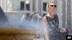 Seorang perempuan berjalan melewati sebuah air mancur di Skopje, Macedonia. Gelombang panas melanda berbagai belahan dunia pada musim panas di belahan bumi utara ini.
