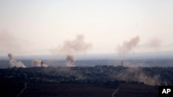 FILE - Smoke and explosions from the fighting between forces loyal to Syrian President Bashar Assad and rebels rise in the village of Jubata al-Khashab as seen from the Israeli-controlled Golan Heights.