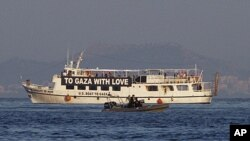"""The activist run boat """"Audacity of Hope"""" is escorted by the Greek coast guard in port of Perama, near Athens, Greece, July 1, 2011."""