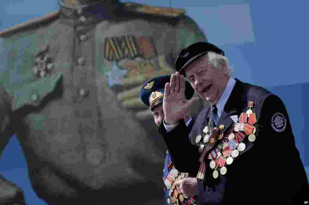 An unidentified Russian WWII veteran salutes as he walks, after the Victory Parade marking the 70th anniversary of the defeat of the Nazi Germany in World War II, in Red Square, Moscow, May 9, 2015.