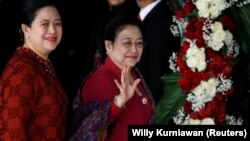 Mantan Presiden Indonesia Megawati Soekarnoputri melambai kepada wartawan saat ia tiba bersama putrinya Puan Maharani, Menteri Koordinator Pembangunan Manusia dan Kebudayaan Indonesia, untuk menghadiri pidato kepresidenan menjelang Hari Kemerdekaan, di ge