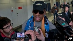 Former NBA star Dennis Rodman, center, arrives at the capital airport for a flight to North Korea, in Beijing, China, Thursday, Dec. 19, 2013.