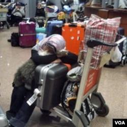 Seorang warga asing menunggu penerbangan di bandara Kairo. Beberapa negara mulai melakukan evakuasi warganya keluar dari Mesir.