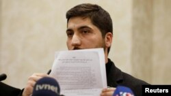 Osama Abu Zaid, a spokesman for the Free Syrian Army rebel alliance, shows the text of the agreement about a cease-fire between Syrian opposition groups and the Syrian government during a news conference in Ankara, Turkey, Dec. 29, 2016.