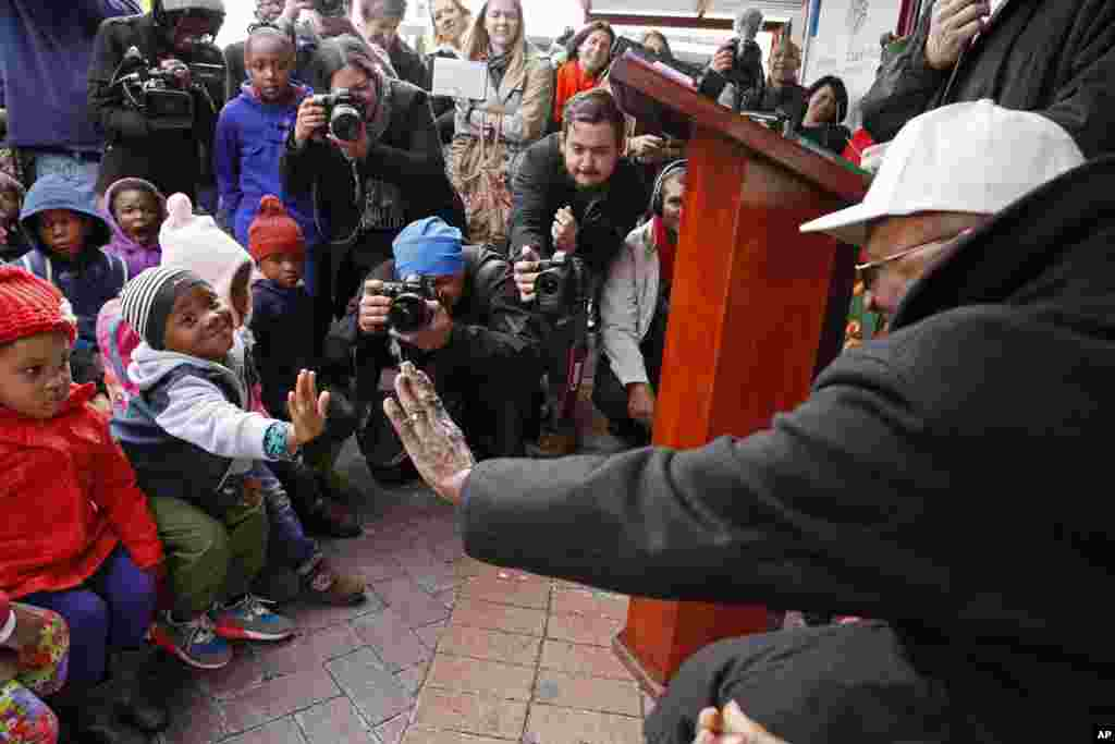 Archbishop Desmond Tutu, right, holds out his hand as he interacts with children during celebrations of former South African President Nelson Mandela's birthday in Cape Town, South Africa, July 18, 2014.