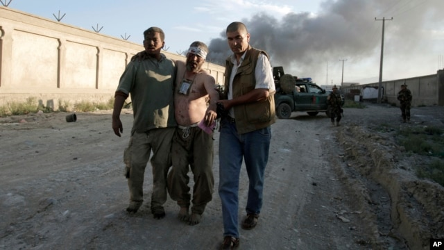 Afghan people assist an injured man after a bombing at the gate to a NATO compound in Kabul, Afghanistan, July 2, 2013.
