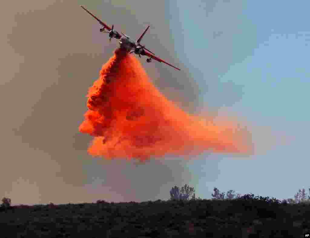 Protupožarni avion izbacuje tekućinu za gašenje velikog šumskog požara u okrugu Lancaster, američka savezna država Kalifornija.
