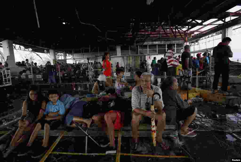 Tacloban residents wait for military flights inside the terminal of Tacloban airport, Nov. 12, 2013.