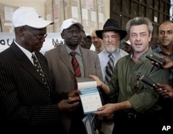 Eamon Omordha, right, Deputy Director of the UN Integrated Referendum and Electoral Division, hands over a referendum ballot to Justice Chan Reec Madut, left, Chairman of the Southern Sudan Referendum Bureau, during a material handover ceremony in Juba 23