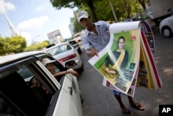 FILE - A street vendor unfolds pages of a calendar featuring Aung San Suu Kyi in a Yangon street, Myanmar, Nov. 12, 2015.