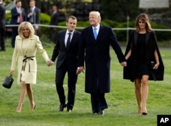 President Donald Trump and first lady Melania Trump walk on the South Lawn with French President Emmanuel Macron and his wife Brigitte Macron at the White House, April 23, 2018, in Washington.