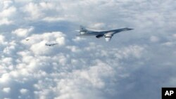 FILE - In this image made available by the Royal Air Force, Jan. 15, 2018, two Russian Blackjack Tupolev Tu-160 long-range bombers are followed by an RAF Typhoon aircraft (L) scrambled from RAF Lossiemouth, Scotland.