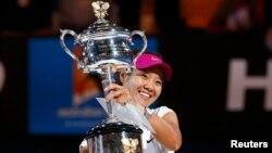 Li Na dari China dengan pialanya setelah mengalahkan Dominika Cibulkova dari Slovakia dalam pertandingan tunggal putri di Australia Terbuka (25/1). (Reuters/Petar Kujundzic)