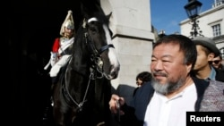 FILE - Artist Ai Weiwei passes a member of the Household Cavalry on duty outside Horse Guards Parade as he walks through central London, Sept. 17, 2015.