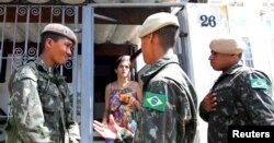 FILE - Brazilian soldiers conduct an inspection for the Aedes aegypti mosquito as part of efforts to prevent the spread of the Zika virus, along a street in Sao Paulo, Brazil, Feb. 1, 2016.