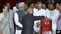 Menteri Keuangan India, Pranab Mukherjee memasukkan surat suaranya di salah satu TPS di New Delhi, disaksikan oleh PM Singh dan presiden kongres India, Sonia Gandhi (19/7).
