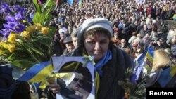 Một phụ nữ cầm bức ảnh của nhà thơ Taras Shevchenko trong cuộc mít tinh đánh dấu 200 ngày sinh của ông gần đài kỷ niệm ông trong trung tâm thủ đô Kyiv, 9/3/14