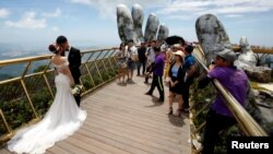 A couple stand near giant hands structure for their wedding photos on Gold Bridge on Ba Na hill near Danang city, Vietnam August 1, 2018. REUTERS/Kham - RC1F1CE07A50