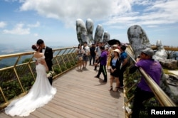 A couple stand near giant hands structure for their wedding photos on Gold Bridge on Ba Na hill near Danang city, Vietnam August 1, 2018. REUTERS/Kham