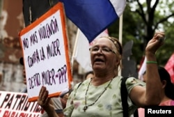 """Women from different social, rural and urban organizations march to commemorate International Day for the Elimination of Violence Against Women, in Asuncion, Paraguay, Nov. 25, 2015. The sign reads """"Stop Violence Against Women."""""""