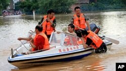 Chinese rescuers try to help residents cross a flooded street in Qinzhou, southwest China's Guangxi province on October 3, 2011.